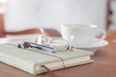 Notebook With Pen, Eyeglasses And White Coffee Cup by punsajaporn